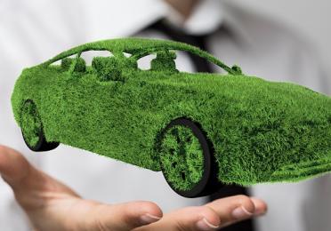 Homme en costume tenant une voiture verte dans sa main