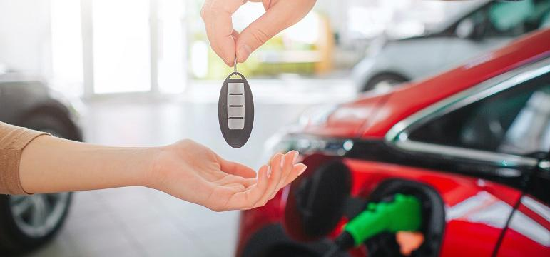 Personne qui reçoit la clé de sa voiture électrique