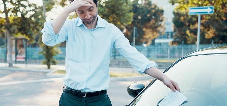 Homme déçu qui trouve un PV sur le pare-brise de sa voiture