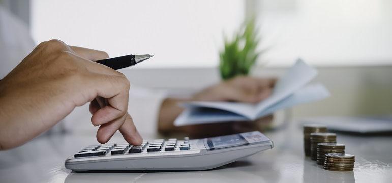 Homme qui calcule sa TVA récupérable avec une calculatrice