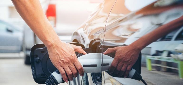 Conducteur en train de recharger un véhicule électrique