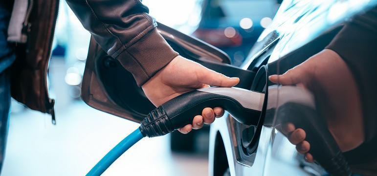 Homme qui recharge sa voiture électrique