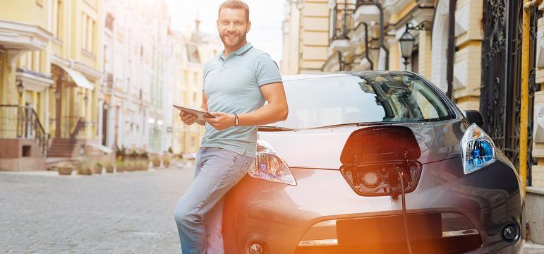 Homme qui attend pendant la recharge de sa voiture électrique