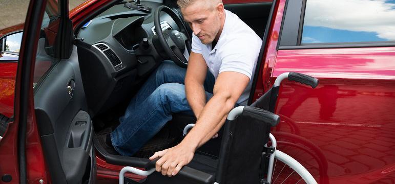 Conducteur assis au volant qui récupère son fauteuil roulant