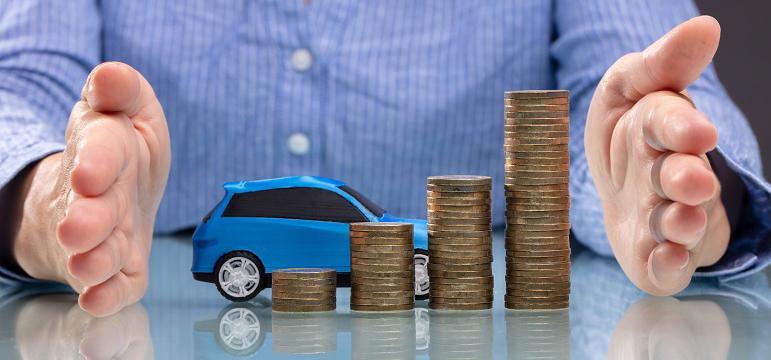 Homme qui a une voiture miniature et des piles de pièces de monnaie sur son bureau