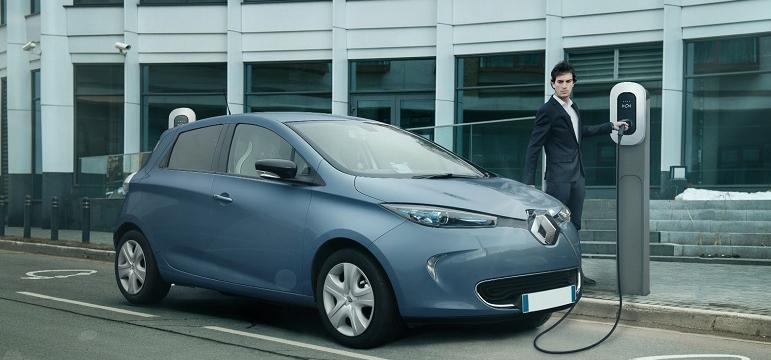 Homme qui recharge sa voiture sur une borne électrique TOTAL