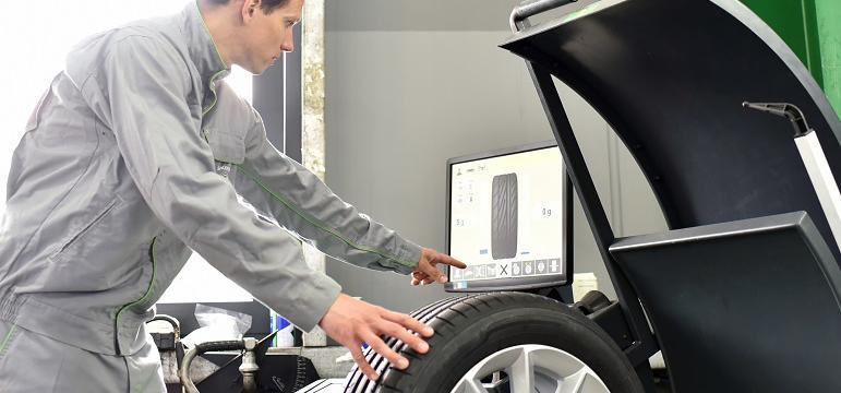 Mécanicien qui vérifie l'état d'un pneu connecté