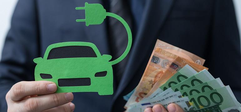 Homme qui tient une voiture électrique et de l'argent en main