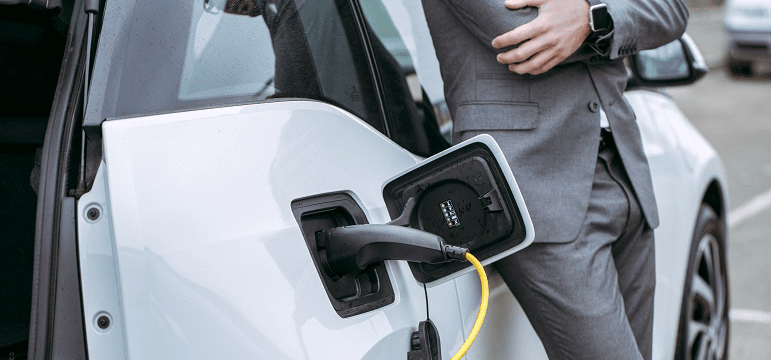 Homme adossé sur une voiture électrique en recharge