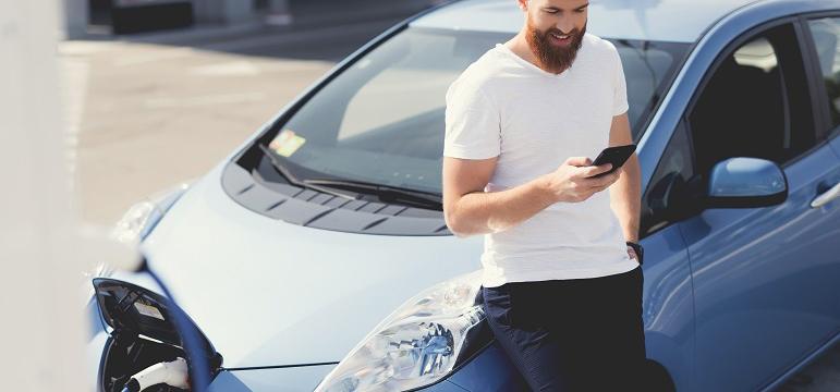 Homme qui regarde son téléphone pendant que sa voiture recharge