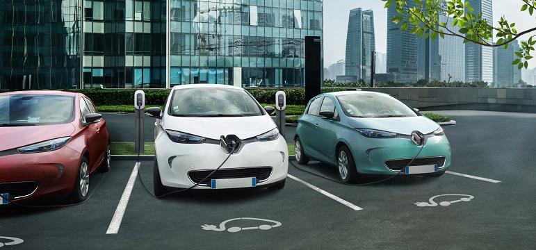 Véhicules électriques en recharge sur un parking avec bornes TotalEnergies