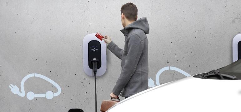 Salarié qui recharge sa voiture électrique sur une borne TOTAL