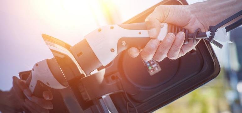 Conducteur qui recharge son véhicule électrique